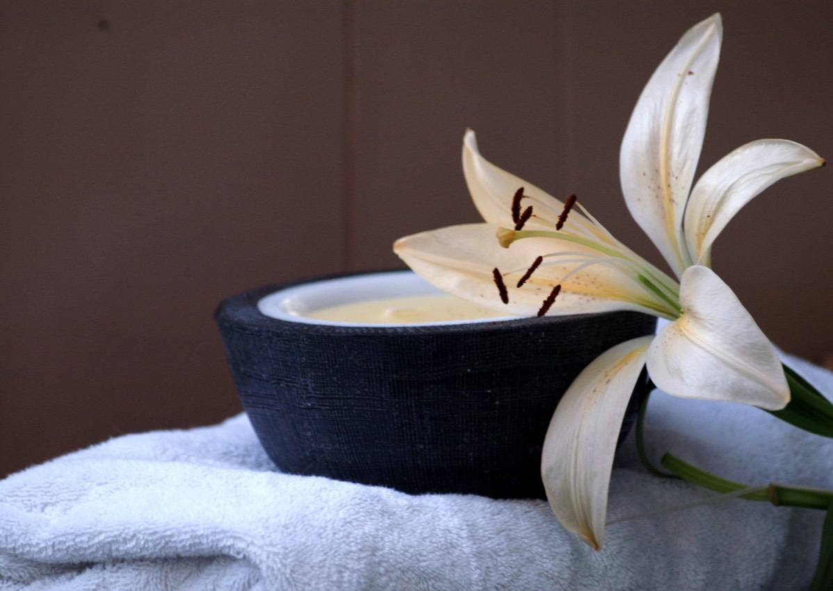 stone bowl of massage cream with flower on top of massage towel